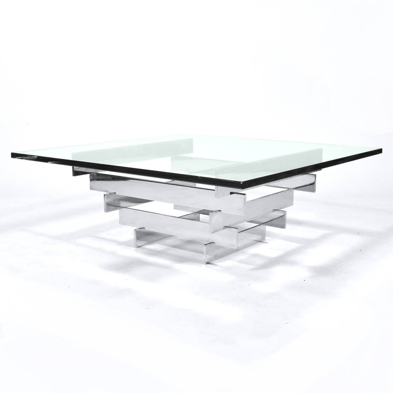 A base of polished chromed steel with a wonderful architectural design supports a substantial glass top this Paul Mayen coffee table perfectly illustrates his refined Minimalist aesthetic.