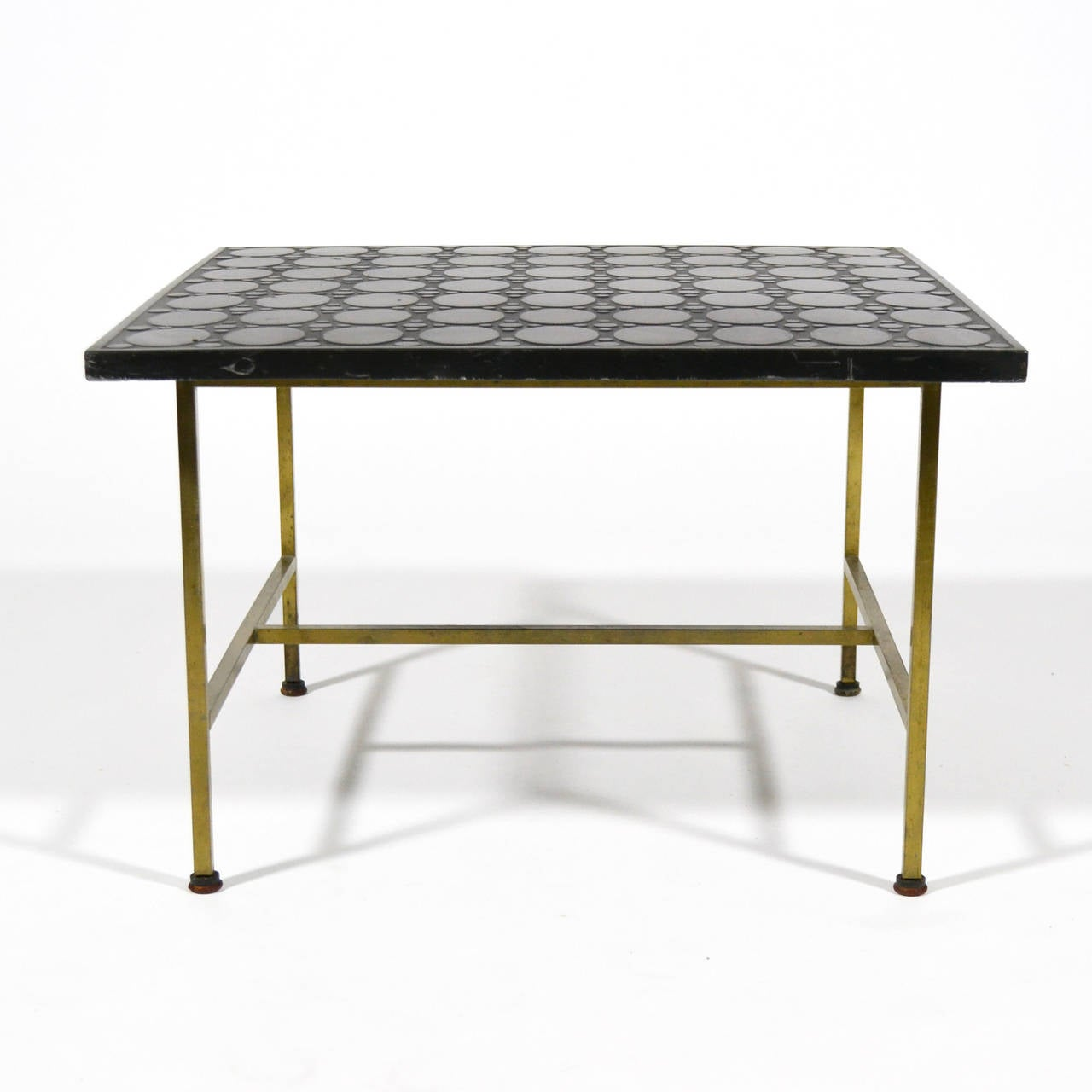 The Paul McCobb side or end table features a brass base and a most unusual top with a wonderful textured pattern. This table is more commonly seen with a travertine or vitrolite top. The rich black top has a delightful pattern of circles and