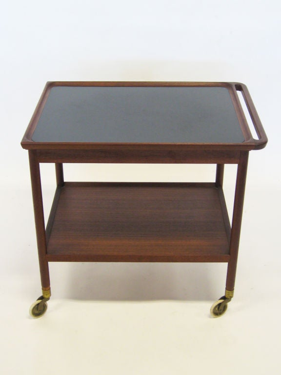 Finely crafted of rosewood with a black laminate top and integrated handle, this serving cart by Pontoppidan is scaled perfectly for a variety of uses.