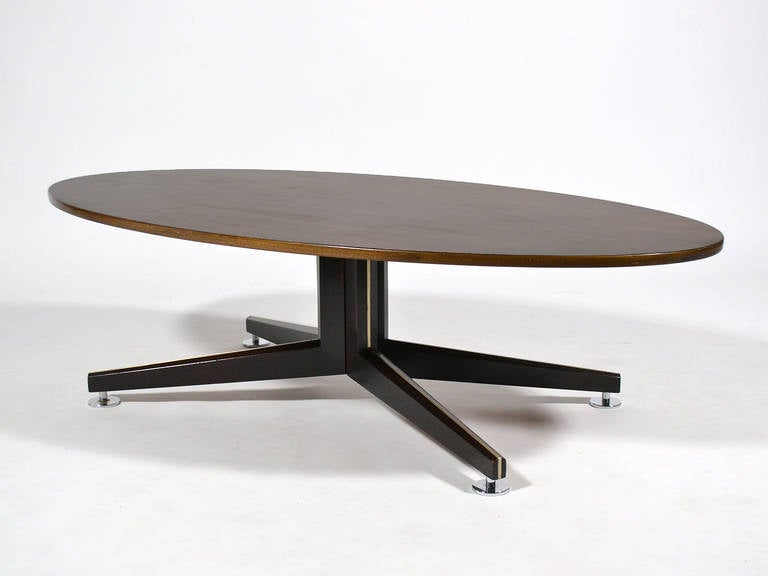 This stunning cocktail table by Edward Wormley exemplifies his refined sensibility and fine detailing as well as the quality of Dunbar's construction. The table was custom ordered with an oval rosewood top supported by a mahogany four-star pedestal
