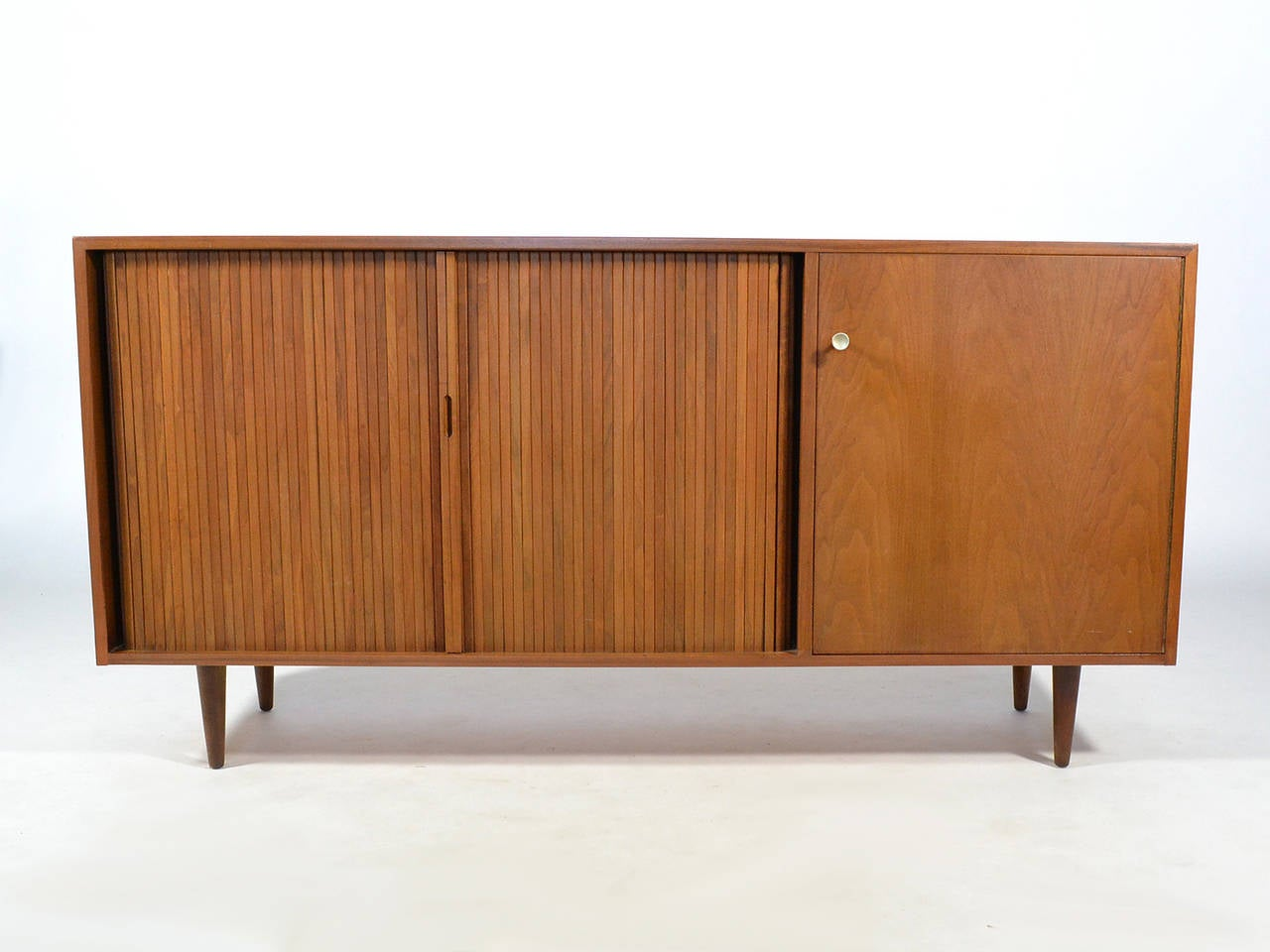This walnut cabinet designed by Milo Baughman for Glenn of California is handsome and highly functional. The asymmetrical arrangement is very attractive. It has a single door which conceals a shallow drawer, a shelf, and two vertical storage