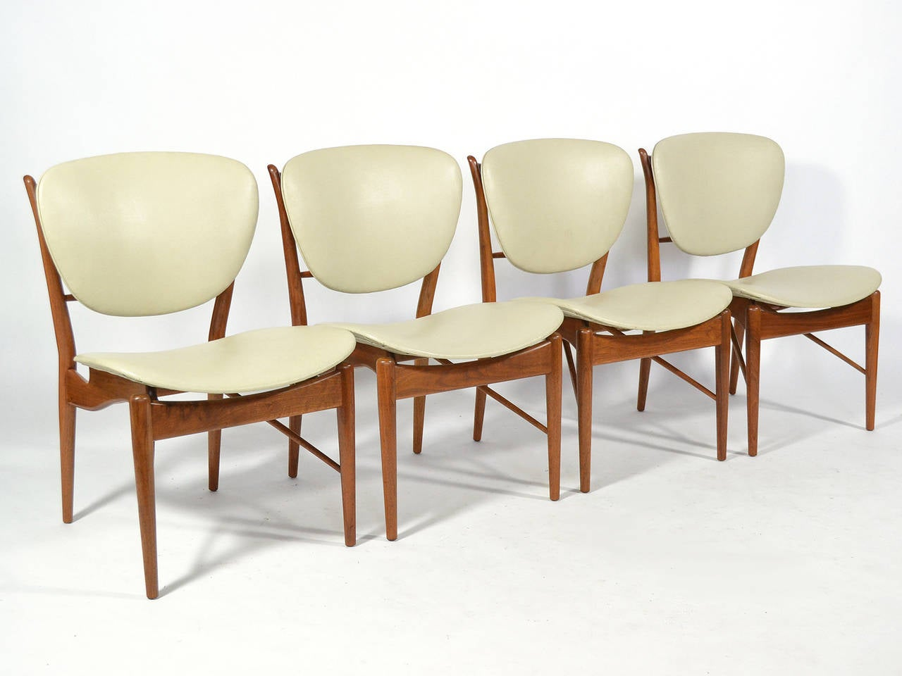 This exquisite dining set by Finn Juhl was designed in 1951 and is Classic Juhl. The sculptural frames of the model FJ 51 chairs support the curved seats and backs giving them the appearance of floating. This separation of the bearing and borne