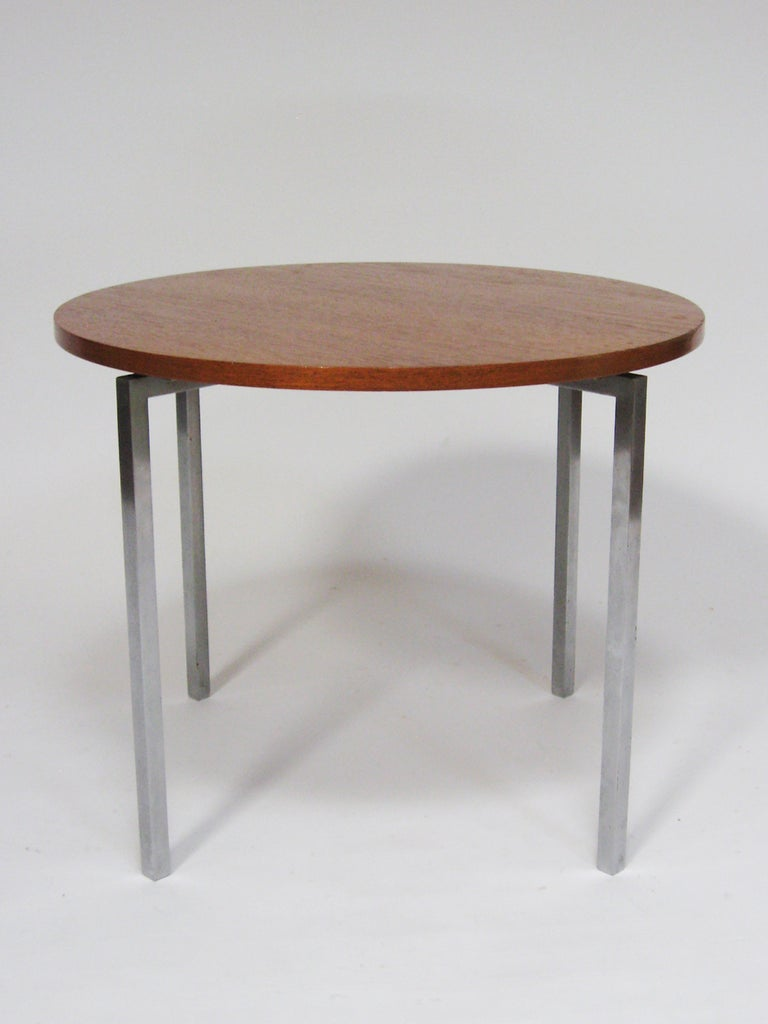 This great little table designed by Florence Knoll perfectly exhibits her highly refined design sensibility and the quality of vintage Knoll production. The round teak top is supported by a solid steel base with a brushed nickel finish. There is a