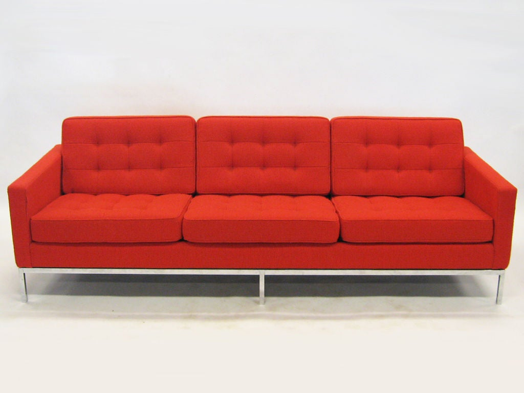 This classic Florence Knoll sofa is as comfortable as it is handsome. Recently upholstered in fire red Cato fabric, this early example has design features which have since been eliminated by Knoll. The sofa has the subtle reveal between the base and
