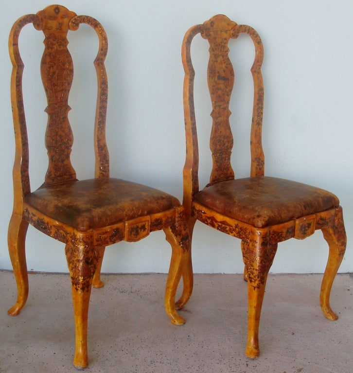 Enchanting pair of carved and painted Portuguese-style side chairs in the Chinese taste with Japanned finished surfaces showing very decorative figural and floral designs, on a saffron finished wood ground with stretched leather upholstered seats.