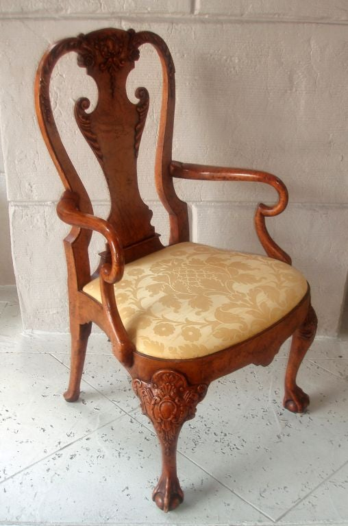 Beautifully carved and polished damask upholstered Queen Anne style burl wood armchair, acanthus leaves flanking the scrolling design on central back support with similarly detailed scrolled frame above with floral motif, rounded arm rests above