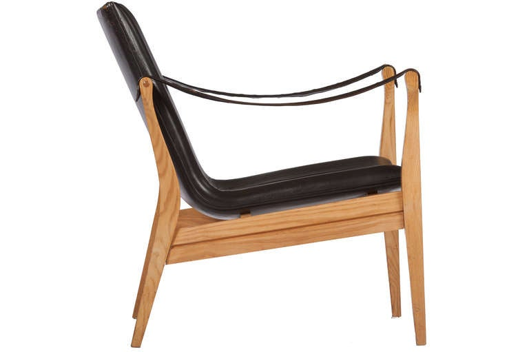 Handsome and well constructed lounge chair in solid ash, with black oxhide sling arms and original leather seat and back. Manufactured by Fritz Hansen.