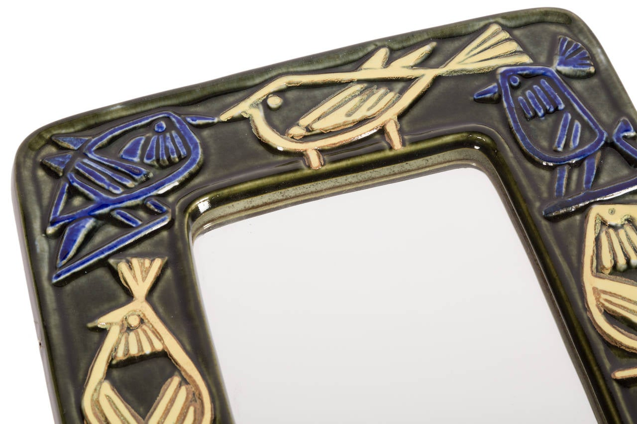 Whimsical Swedish Modern ceramic mirror by Lisa Larsen for Gustavsberg. With multicolored birds in relief. Signed.