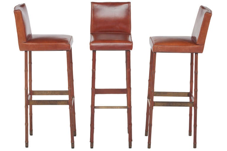 Elegant set of three tall leather wrapped bar stools designed by Jacques Adnet in a beautiful patinated brown leather. Leather wrapped legs and seats, also with brass-plated steel foot rests.