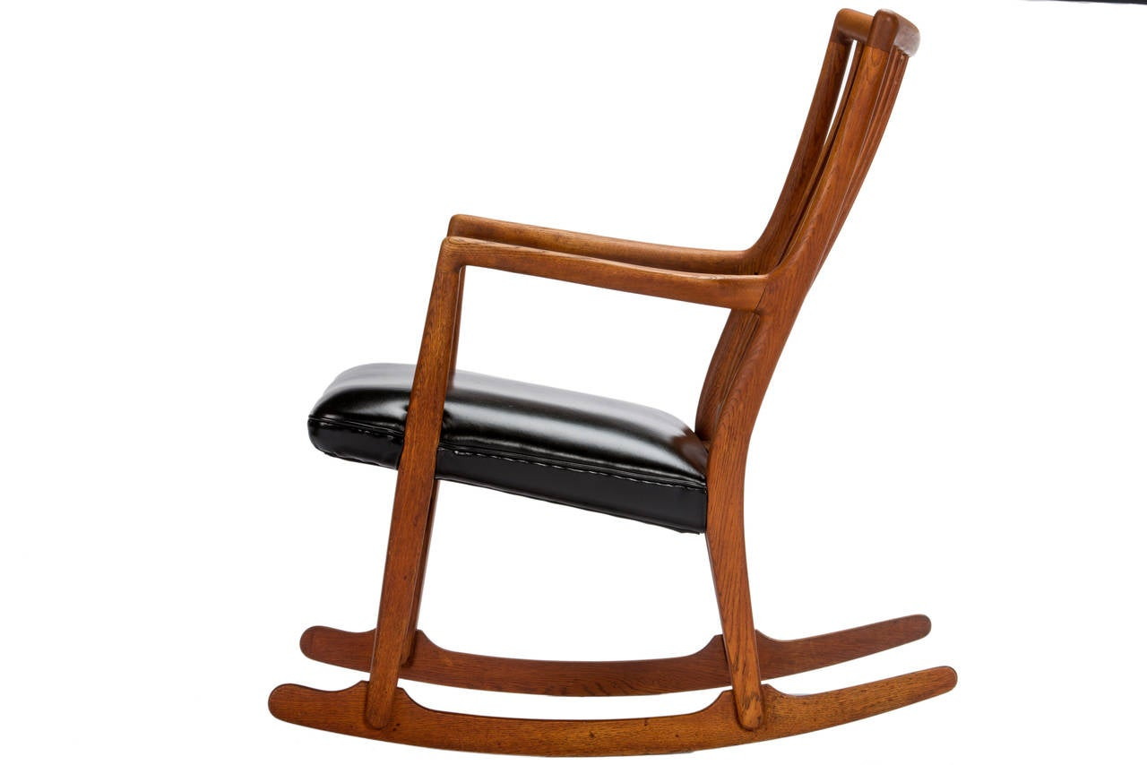 Early Wegner rocker in oak with new black leather. This chair is Hans Wegner's first rocking chair design, collaborating with Mikael Laursen in the mid-1940s.