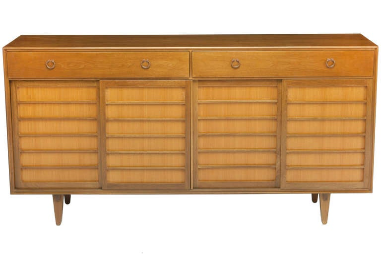 Beautiful Japanese-inspired sideboard or credenza designed by Edward Wormley, manufactured by Dunbar. Walnut cabinet features four sliding Japanese pine doors. Interior with two shelves, pull-out trays and two large partitioned drawers with forged