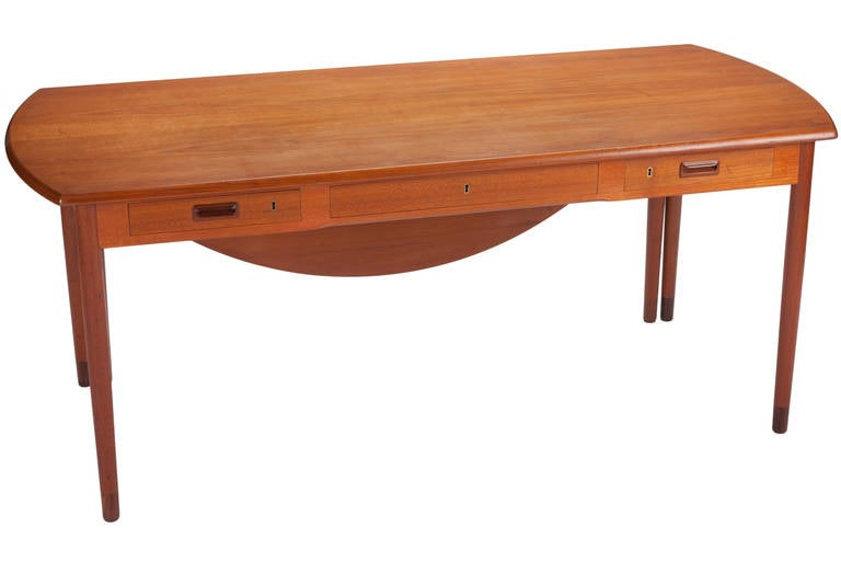 Interesting and rare Danish designed desk by A. Bender Madsen and Ejner Larsen and manufactured by Willy Beck. Desk features a 21-inch drop-leaf. Table measures 31 inches when folded. Inset rosewood handles. Signed with applied manufacturer's label