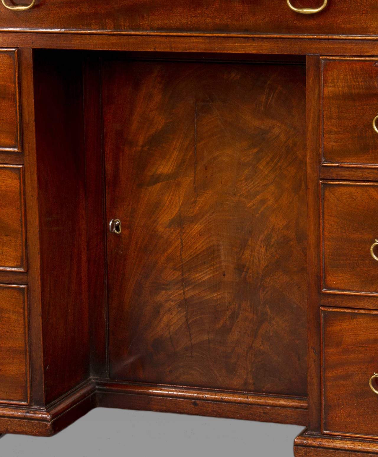 With one long drawer to the frieze over two columns of three short draws with a recessed cupboard between ending in the original bracket feet. This small desk is of excellent quality and craftsmanship constructed of well figured dense Cuban
