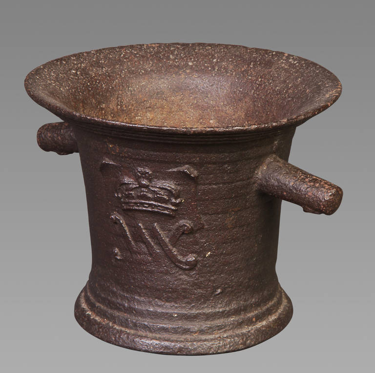 A late 17th century iron mortar of large proportions with sharply everted rim and corded, slightly tapering sides, with two lug handles, cast to either side with the cipher 'VM' beneath a crown for William and Mary, on a spreading moulded foot.