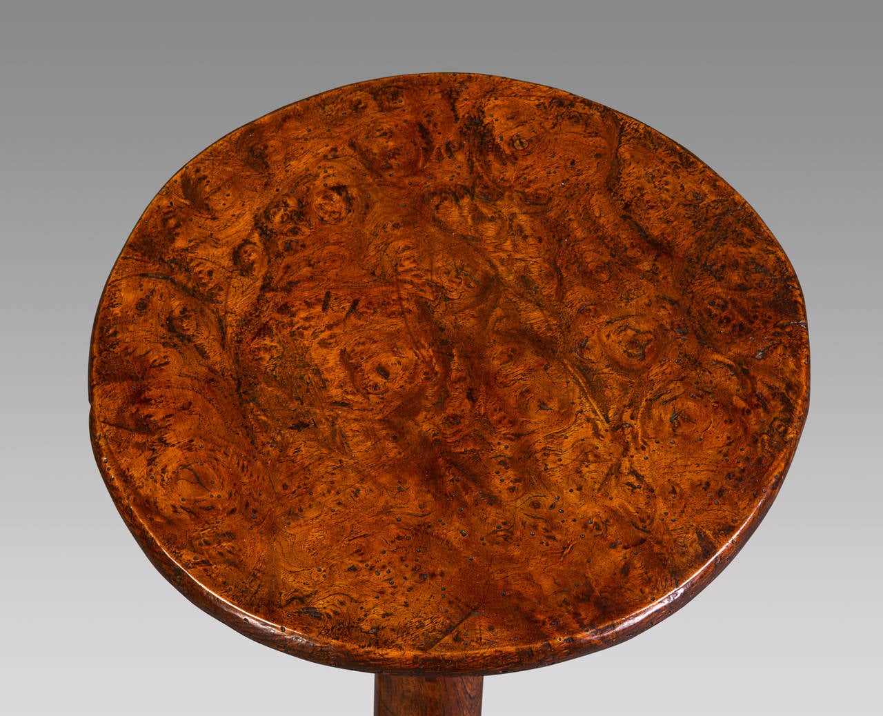 A wonderful piece of superb design with a diminutive top and strongly splayed legs, crafted in solid elm, the decorative drop at the base of the column points to the 19th century origins of this lovely table. The single piece burr elm top retains a