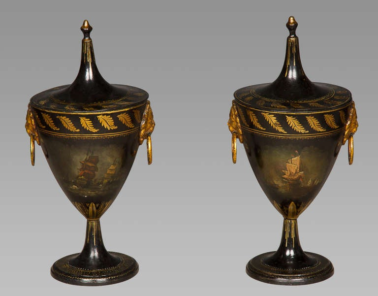 A delightful pair of Regency period tole-work covered chestnut urns in good original condition with very minor in-painting. Each is painted to one side with a naval scene, to the other with a house in a rural landscape, and both with twin lion's