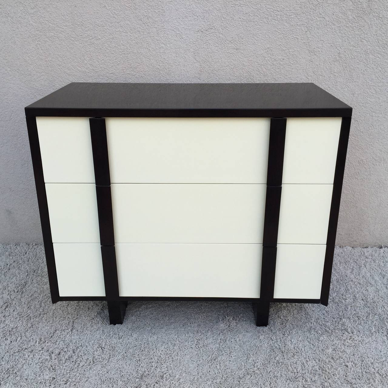 Pair of Paul Laszlo dark walnut off-white lacquered chest of draws with dark walnut pulls, hand rubbed finish.