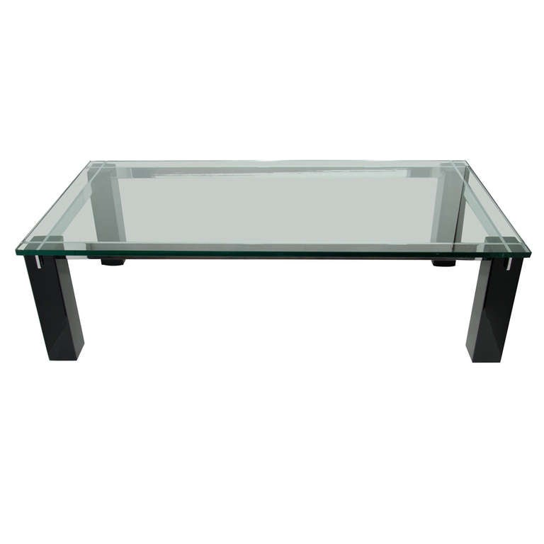 Large Mid-Century Modern coffee table with architectural design. Features heavy glass top over ebonized mahogany wood block base. Chromed steel bars are inset into the block wood legs vertically and horizontally, creating a crossbar designs.