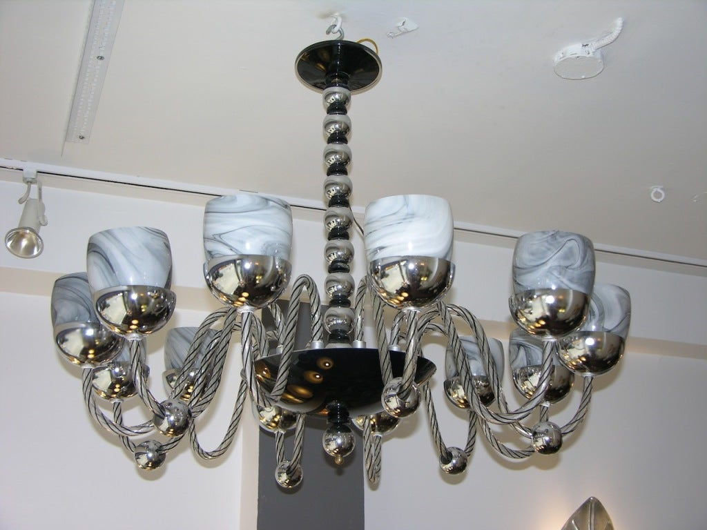 a rare 12 lights vintage Murano glass chandelier, the stem with chromed metal spheres and black Murano glass accents, the black glass bowl holding very elegant blown glass arms worked with black reticello and six decorated with a chromed sphere,