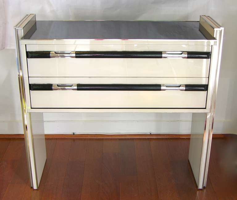 This is a very chic vintage small console/side table with two drawers, entirely edged with chromed metal lines, the surround is all black and ivory white glass. The design is extremely attractive and interesting as the central body looks suspended