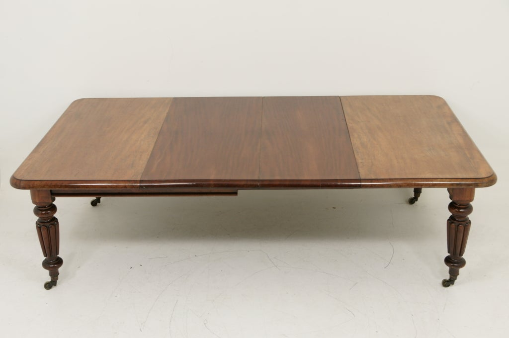 Victorian mahogany extending dining table with two (2) leaves.  The moulded rectangular top over plain frieze raised on fluted tapering legs terminating on ceramic castors.  Table is very sound but it needs to be refinished.<br /> The leaves