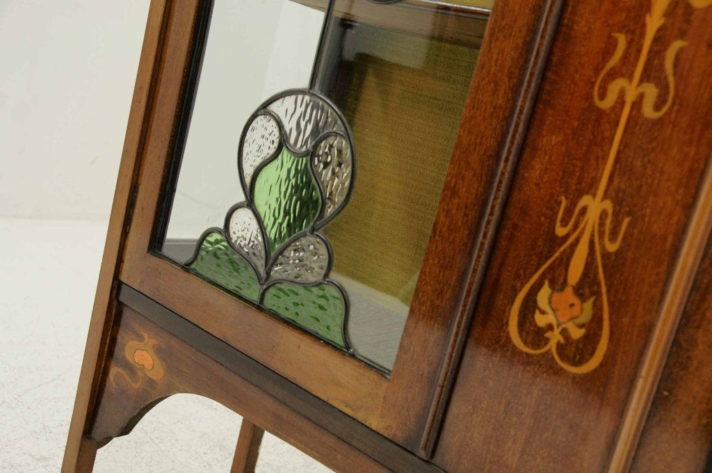 Beautiful early 20th century mahogany inlaid Art Nouveau display cabinet, inlaid ledgeback top above a pair of Art Nouveau stained glass doors, enclosing three (3) interior shelves and ending on tapered legs.  Shipping will be $450.00 - $500.00 by
