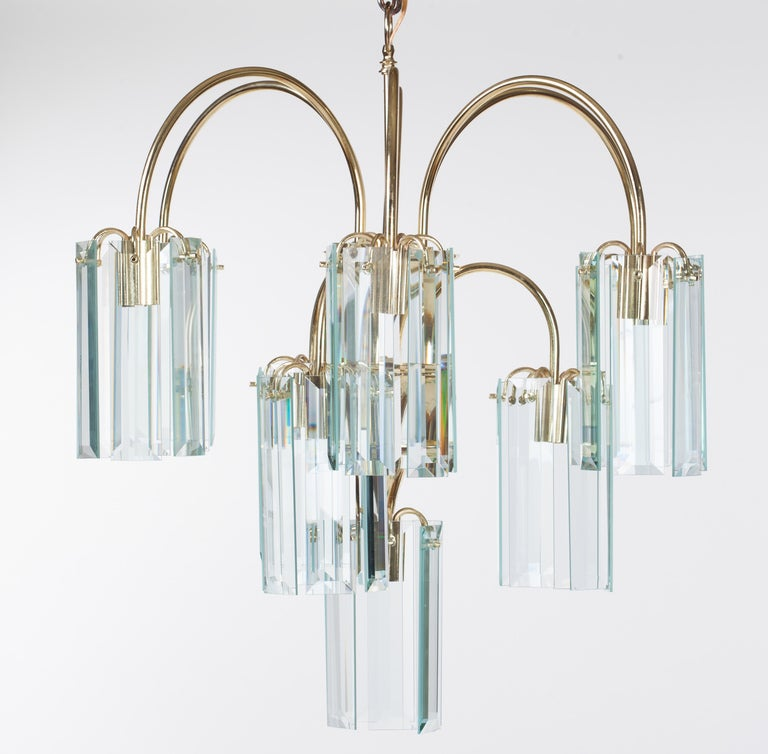 Waterfall form brass chandelier with rectangular beveled glass prisms, circa 1980.