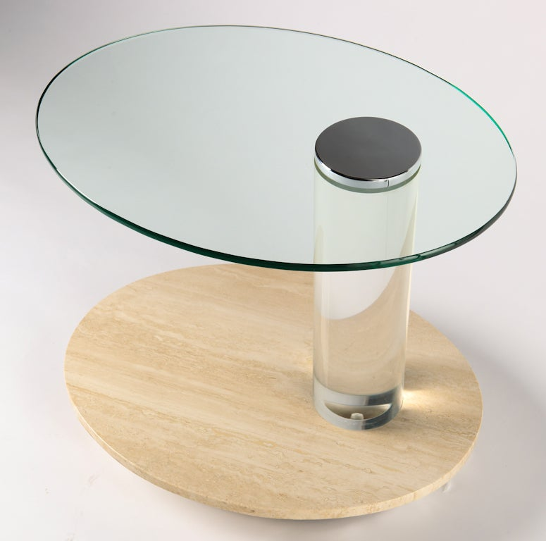 Oval side table has glass top with round chrome cap, lucite column, travertine lower shelf and metal base. Wheels underneath for ease of movement. May be used as bar cart. From a Lake Shore Drive, Chicago estate.