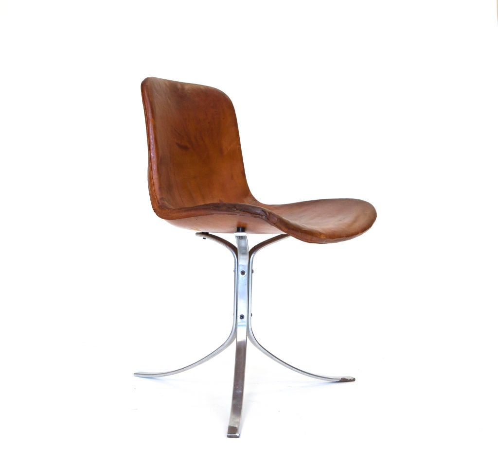The legendary PK9 chair, designed by Poul Kjaerholm in 1960. This chair was manufactured by E. Kold Christiansen with the rare original cognac leather, and its magnificent patina.  It is said, that Kjaerholm's incessant quest for the perfect shape