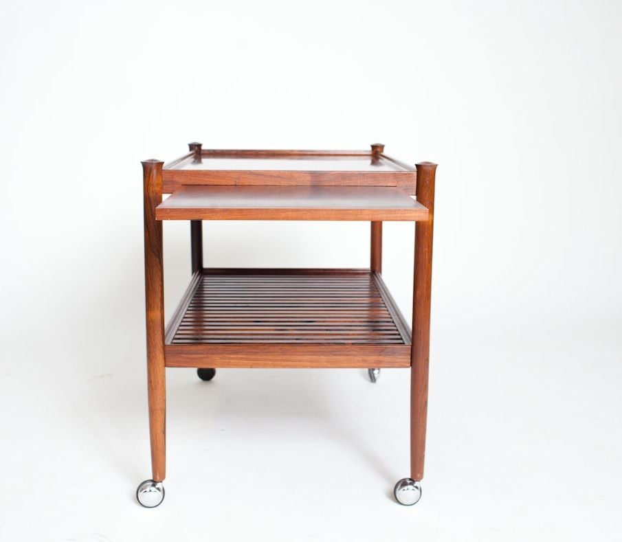 Poul Hundevad designed Rolling Table-Side Cart, circa 1960. Cocktails anyone? This vintage rosewood rolling cart is outfitted with everything you would need for serving in style. From the pull- out tray to the swivel chrome casters this piece brings