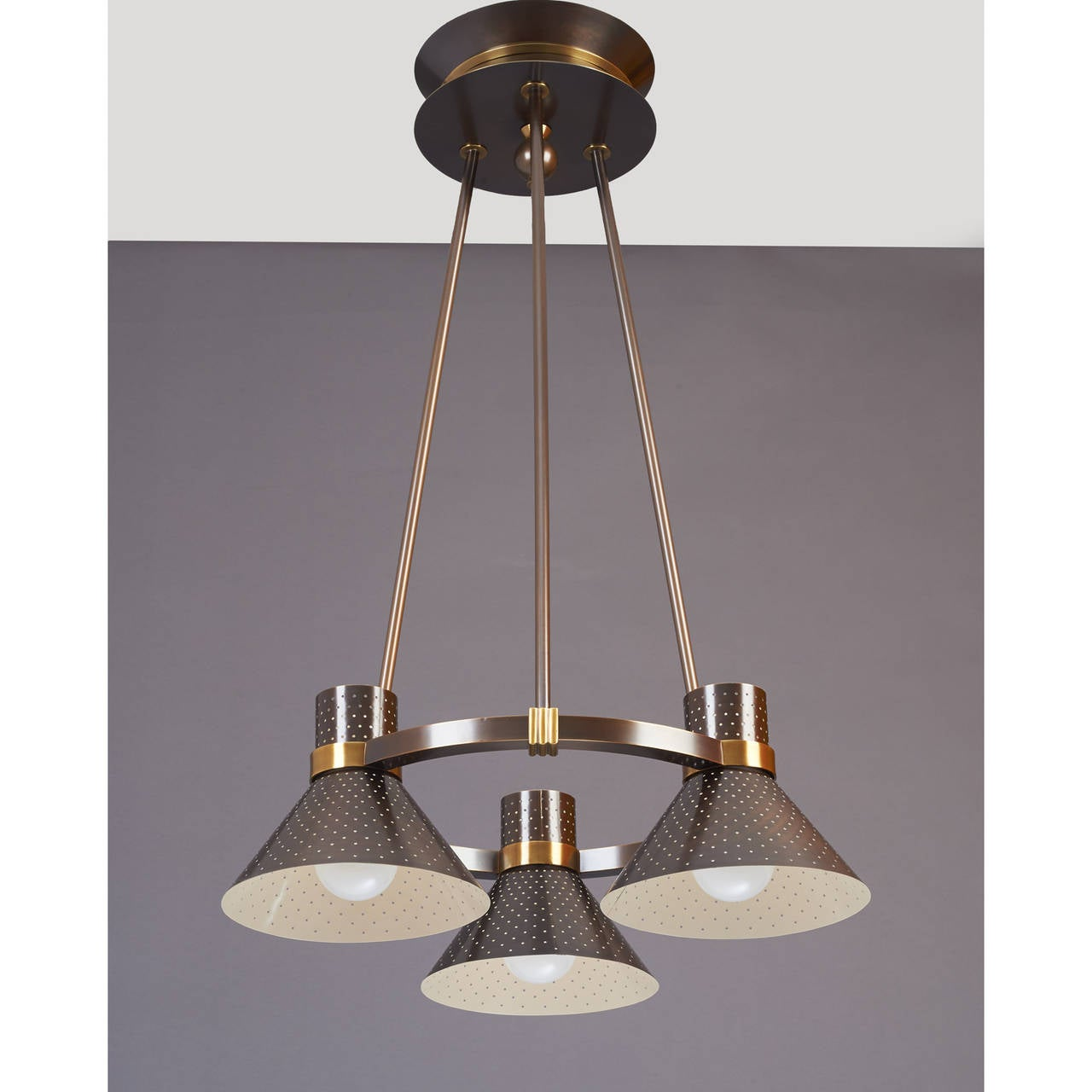Modernist three-light chandelier with perforated metal shades.