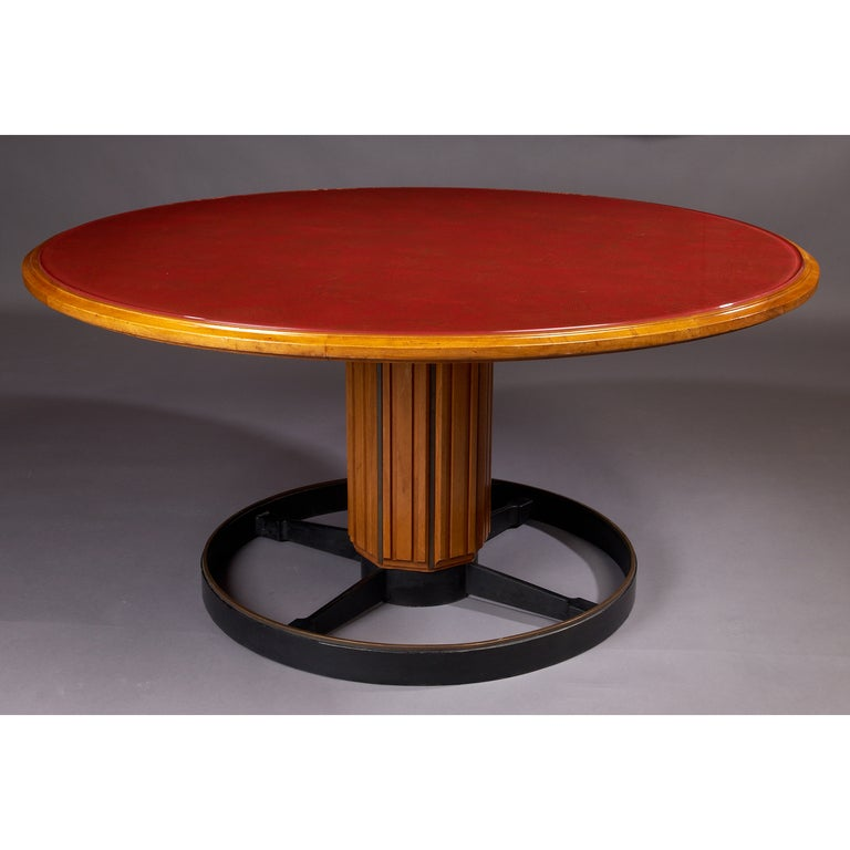 Italy, 1950s. A magnificent pedestal table in fruitwood with framed back-painted glass top in combed red lacquer and gold leaf, an extraordinary evocation of Futurist graphics. Raised on a faceted pedestal in fruitwood on a patinated steel and