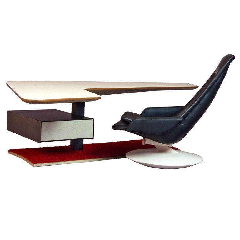 Swiveling boomerang formica top cantilevered over steel column with spring loaded compartmentalized drawer and original shag carpeted base. Black leather upholstered adjustable chair on rocking base. This is a low desk, incredibly comfortable to use