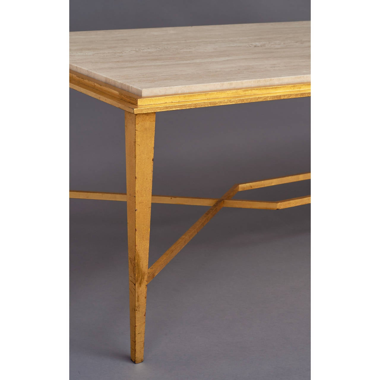 Ramsay. Important long gilt wrought iron table with stepped frame and geometric stretcher. Polished travertine top. Signed, France, 1950s. Dimensions: 63 x 24 x 18.5 H.