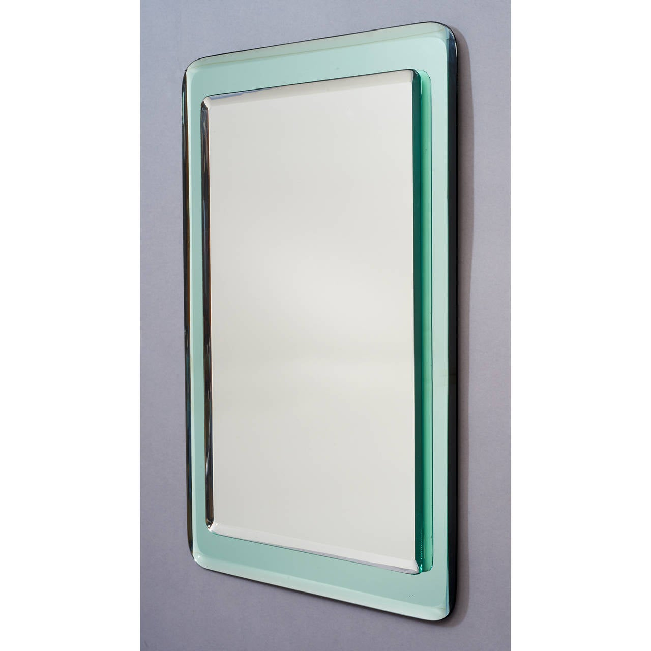 Italy, 1970s. Elegant pair of reverse beveled mirror mounted on reverse beveled colored vert-de-nil mirrored glass, with rounded corners. Dimensions: 19.5 x 28. Two available, sold and priced individually