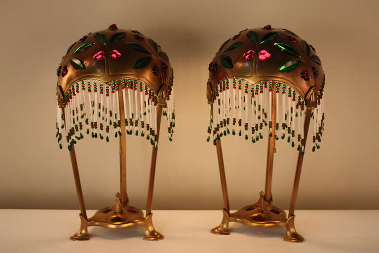 A stunning pair of bronze Art Nouveau table lamps with colored inset glass by Geschutzt.
