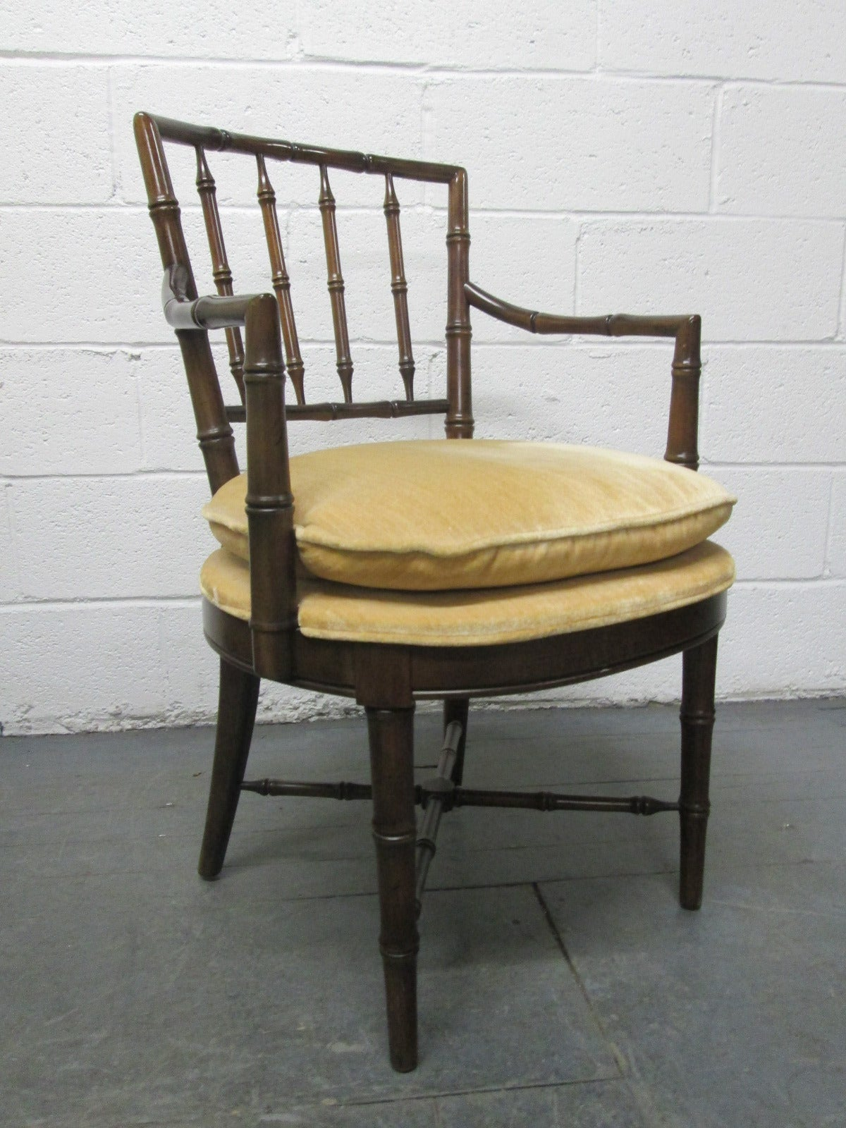 Four faux bamboo armchairs. Has a Chippendale style. Has attached cushioned seats.