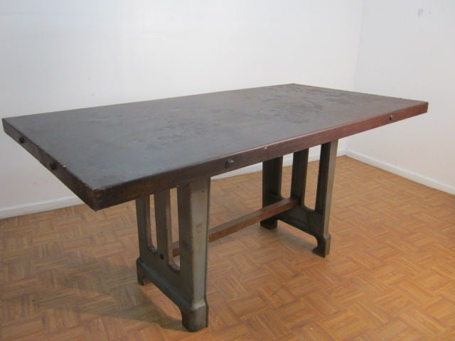 Large steel top table with an industrial base.  Has a wooden stretcher.