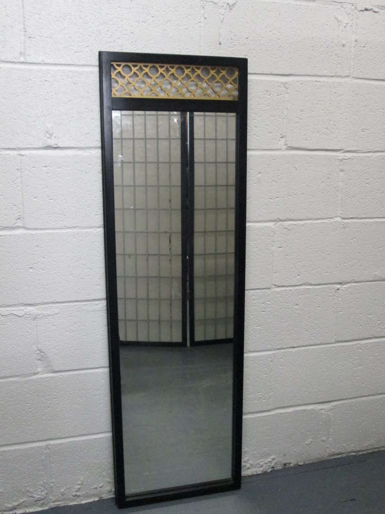 Pair of chinoiserie mirrors in the manner of James Mont. Hollywood Regency. Black lacquered wood frames with gold decorative molding to the top. Has a rectangular shape.