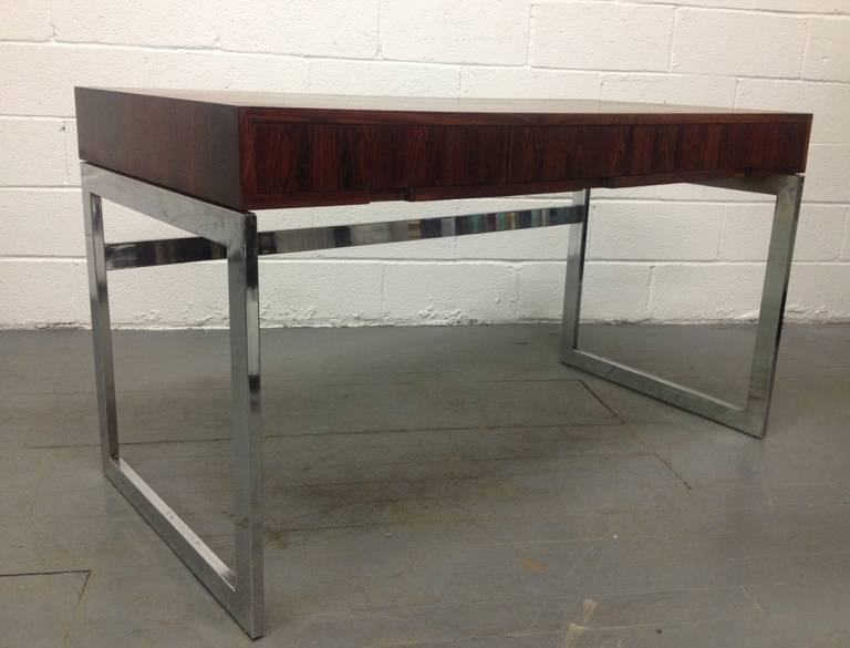 Milo Baughman style rosewood and chrome desk. Desk has three hidden drawers and a beautiful cubed chrome steel base. Nice lines.