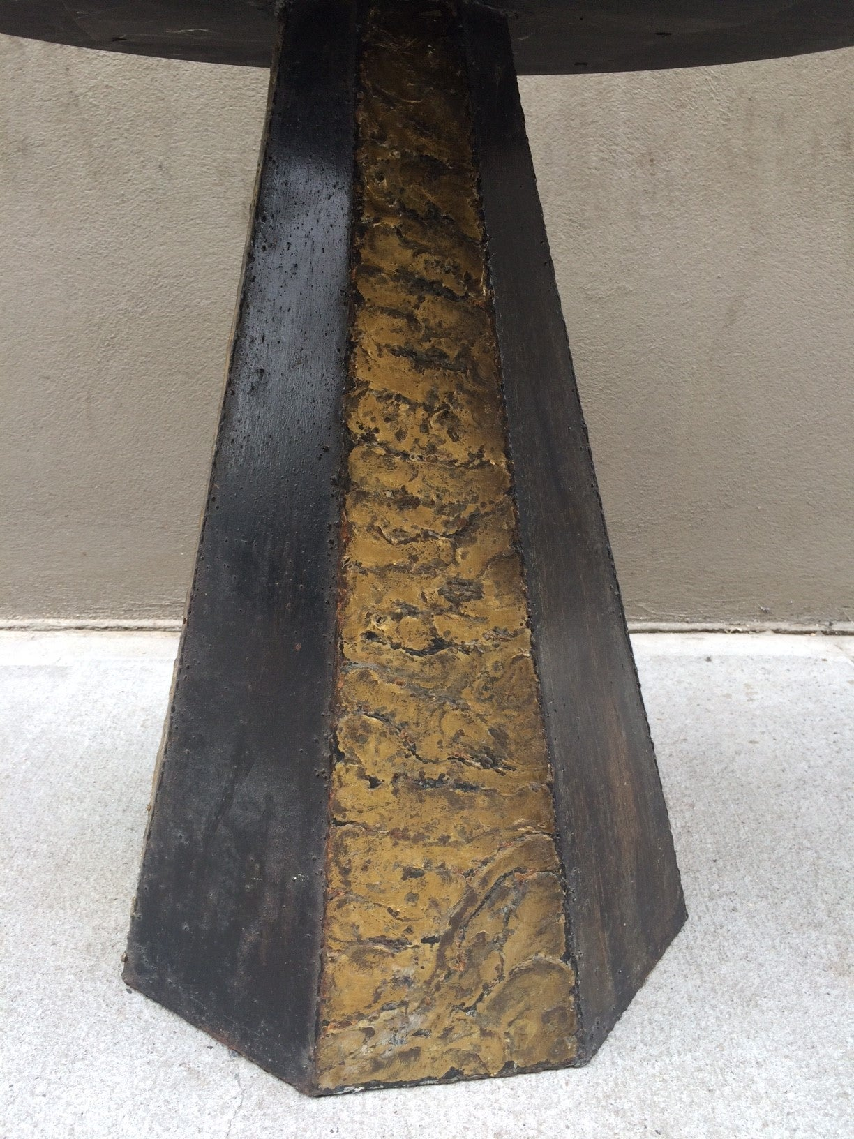 The table has a braised bronze and blackened steel base. The slate top rests upon a steel base which is attached to an apron and has a gold leaf trim. Original slate top.