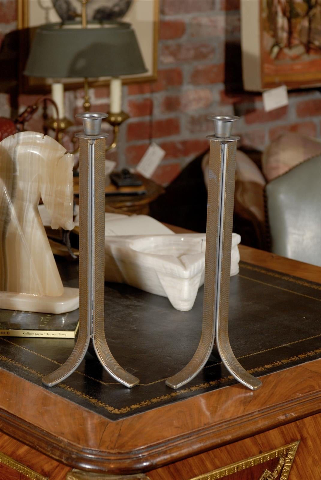 Early 20th Century pair of hand forged steel candlesticks of the Art Deco period with gilt painted geometric fan-shaped decorations on three sides terminating in down swept feet.
