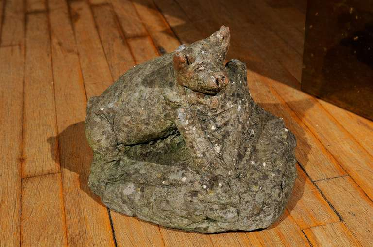 Charming English concrete garden ornament of a piglet resting against a wooden fence