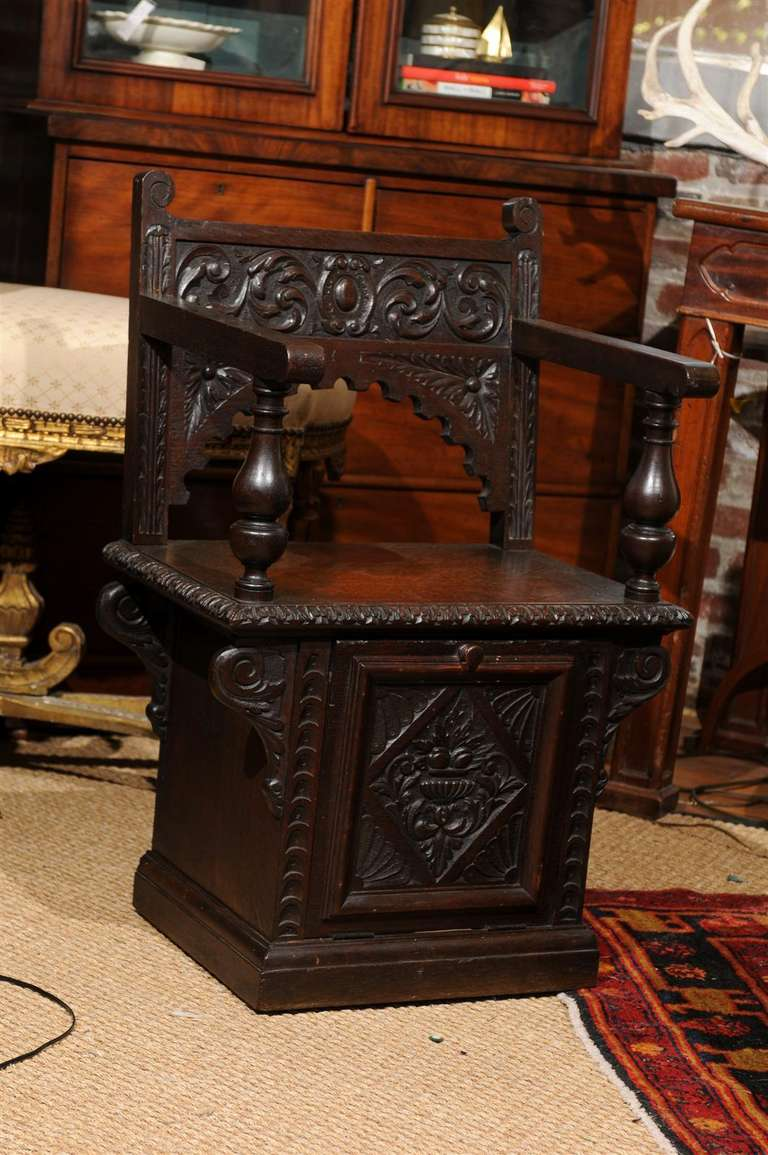 19th Century Italian Renaissance Revival carved oak cabinet chair with built in coal hod (and original liner) beneath the seat.   This chair is one of few surviving examples, as these chairs served a utilitarian purpose residing fireside and storing