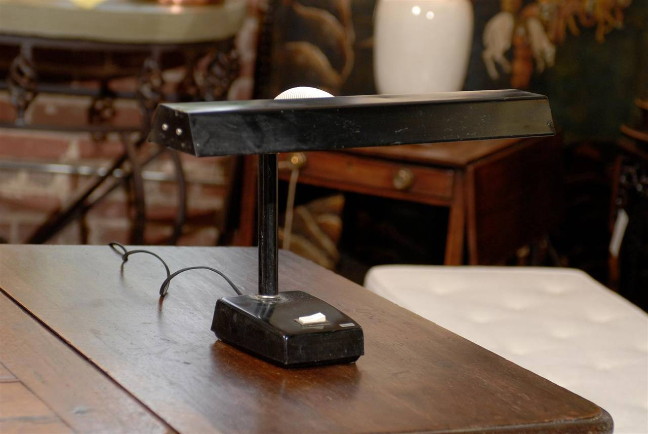 Mid Century Modern black metal desk lamp with white adjustable arm, white switchplate on base, and original Tensor label.