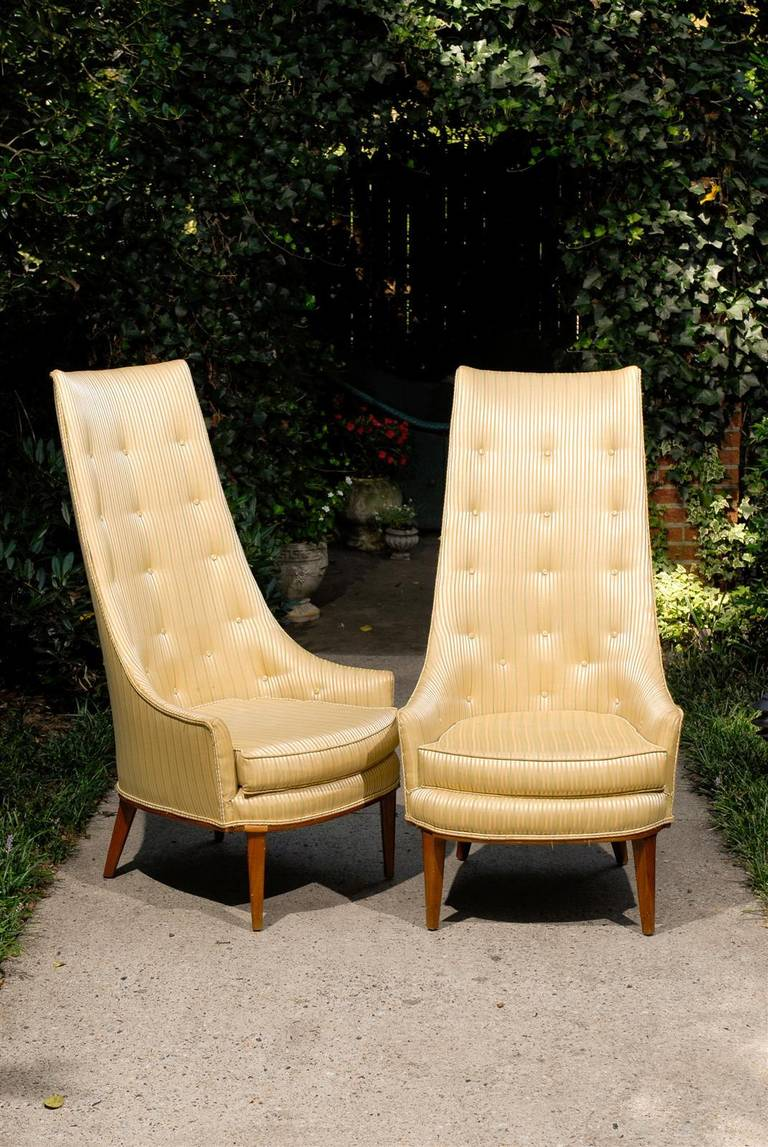 American pair of Mid-Century Modern high back tufted slipper chairs with a loose cushion and resting on a wooden base with tapering legs. The chairs were introduced to the Tomlinson Furniture Sophisticate Collection in the 1960s and were designed by