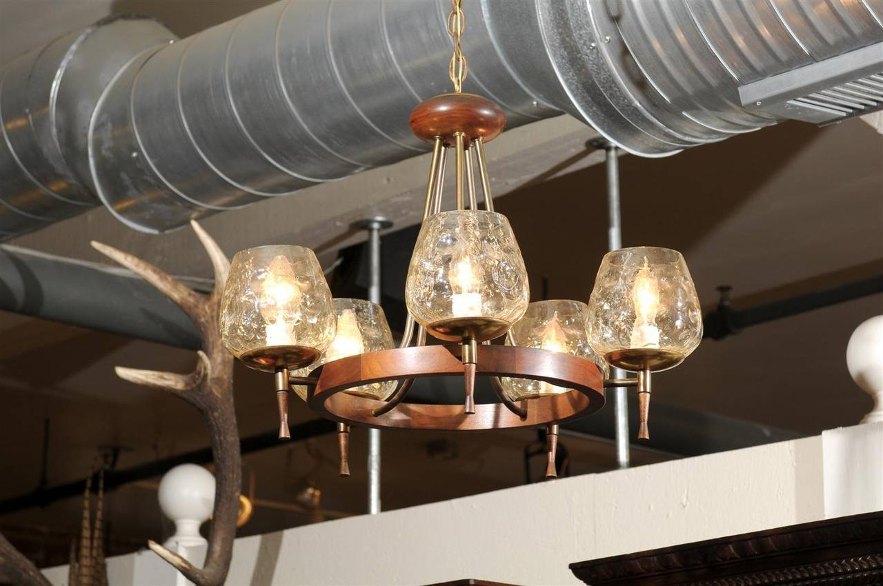 Mid century five light chandelier of teak and brass with champagne colored glass globes having an iridescent pearl finish and of a hammered shape.