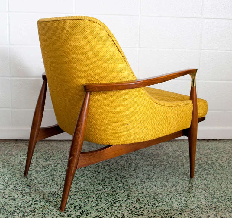 A rare, sculpted arm chair by Ib Kofod-Larsen with wonderful brass arm-joint detail. Original upholstery.