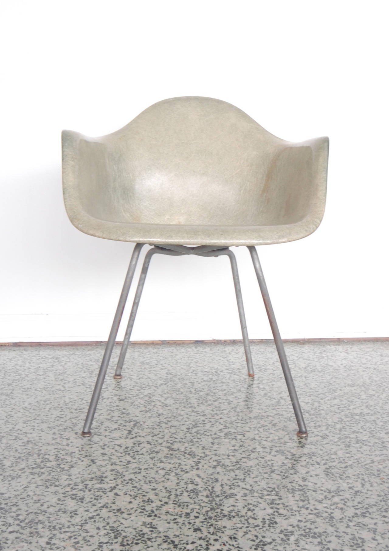 Faded green patina color gives this chair a grey color with solid X bases of an intermediate height with