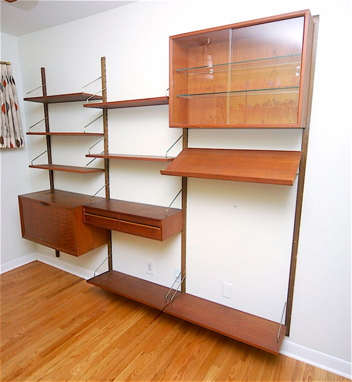 Danish Modern teak Poul Cadovius wall unit for Cado with drop down desk, two drawers, three shelf glass display cabinet, 7 shelves and one display rack.